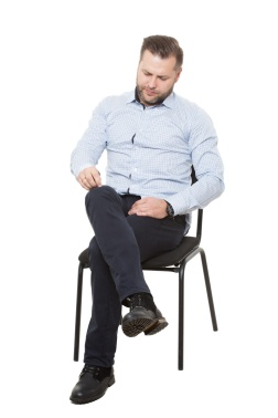 man sitting on chair. Isolated white background. Body language. picking nonexistent lint